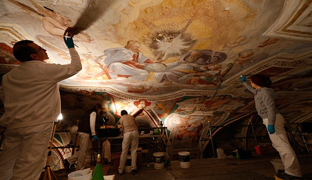 Restorers work on the ceiling of the San Lorenzo Chapel adjacent to the Holy Stairs in Rome March 11. Layers of grime on the chapel's Renaissance frescoes are being removed, bringing the original splendor of the artwork back to life. The project, which w ill include frescoes surrounding the Holy Stairs, is expected to last another five years. / Photo: (CNS photo/Paul Haring) (March 24, 2014)