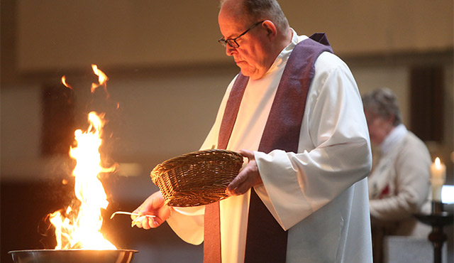 FATHER THOMAS KOMMERS OF ST. JOSEPH CHURCH IN RED WING, MINN., PUTS PALMS IN A BOWL AND BURNS THEM DURING AN ASH WEDNESDAY PRAYER SERVICE FEB. 10. / PHOTO: (CNS PHOTO/DAVE HRBACEK, THE CATHOLIC SPIRIT)